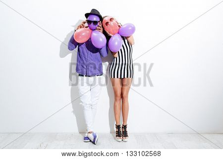 Young funny couple in sunglasses holding balloons having fun isolated on white background