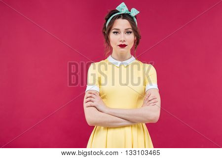 Beautiful serious young woman in yellow dress standing with arms crossed over pink background