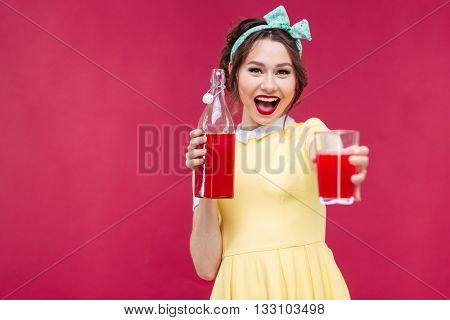Happy beautiful pinup girl in yelow dress giving you a glass of juice over pink background