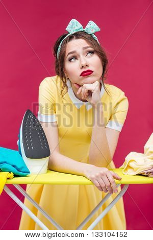 Thoughtful unhappy pinup girl ironing clothes over pink background