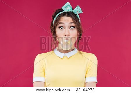 Amazed cute pinup girl in yellow dress blowing a bubble gum balloon over pink background poster