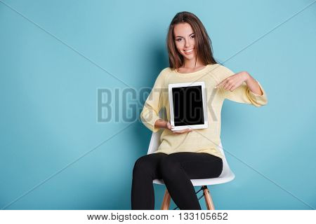 Beautiful young smilling girl pointing at the blank screen isolated on the blue background