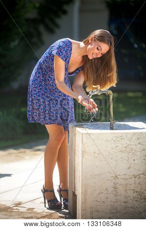 Young pretty woman washing hands in street faucet