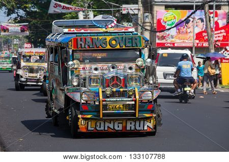 LEGAZPI PHILIPPINES - MARCH 18 2014: Jeepneys passing Filipino inexpensive bus service. Jeepneys are the most popular means of public transportation in the Philippines.
