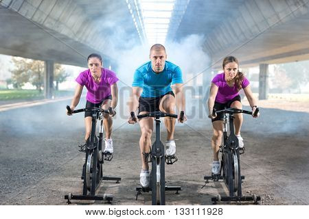 young fitness people riding exercise bikes