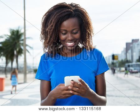 Laughing african woman in a blue shirt sending message with phone outdoor in the city