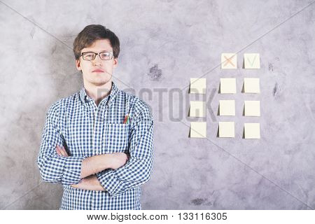 Serious caucasian male with crossed arms looking next to stickers with cross and tick glued onto concrete wall