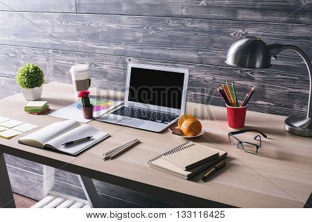 Side view of creative designer desktop with blank laptop stationery items lamp orange and chocolate on plate and other items on wooden background. Mock up