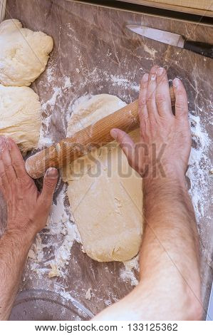 Man working on unfinished dough with a rolling pin
