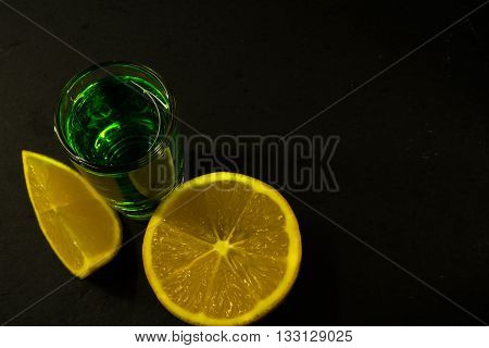 Absinthe and lemon on black background. Alcohol drink. Green alcohol drink