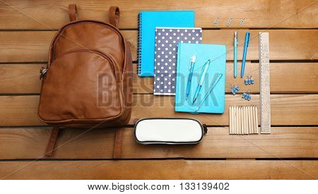 School set with backpack, shoes and supplies on wooden background
