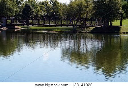Pedestrians may walk over a bridge over an isthmus in the pond in Settlers' Park in Plainfield, Illinois.