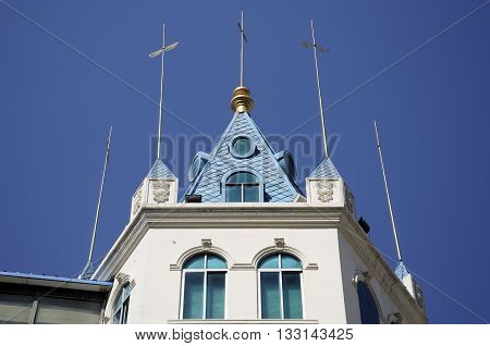 Gold lightning rods on top of a building against a blue sky on Zhongyang street in harbin China within Heilongjiang province.