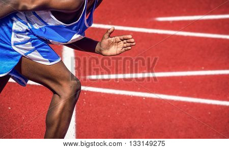 Graphic contrast image in bright sunlight, of a runner on the track, at the beginning of a race