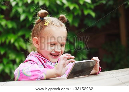 Outdoor portrait of cute blonde toddler girl using a digital tablet or smart phone.