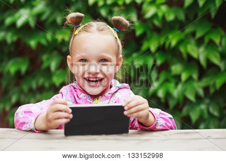Outdoor portrait of cute blonde toddler girl, laugh and using a digital tablet or smart phone.
