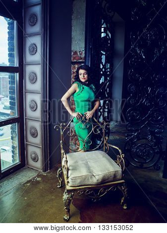 brunette woman wearing a green dress in the room with old walls and furniture