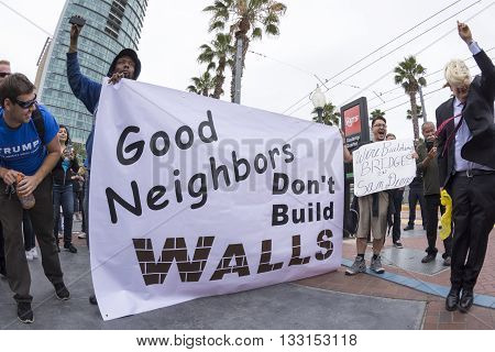 SAN DIEGO USA - MAY 27 2016: Anti-Trump protesters display their opinion about the wall while a Trump fan smiles at their efforts during a protest outside a Trump rally in San Diego.