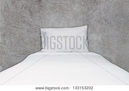 Close up white bedding and pillow on abstract gray concrete texture background