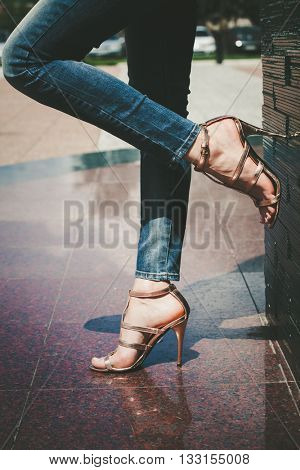 woman legs in blue jeans and high heel golden sandals outdoor shot in the city