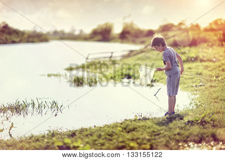 Boy by a river with a fishing net catching fish in the summer sun concept for childhood, healthy lifestyle and vacation