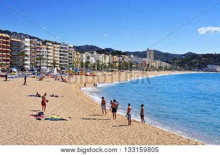 LLORET DE MAR, SPAIN - MAY 22: Sunbathers at Platja de Lloret beach on May 22, 2015 in Lloret de Mar, Spain. It is the main beach in this popular tourist village in the Costa Brava, in Catalonia