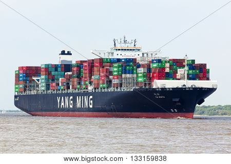 Stade, Germany - May 22, 2016: Ultra Large Container Ship YM Worth on the Elbe river near Hamburg. It is 368 meters long and operated by chinese shipping company Yang Ming Lines, Keelung.