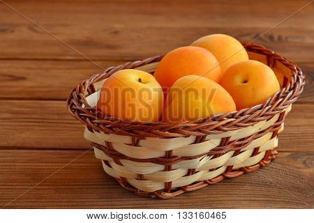 Ripe bright apricots in beige basket on brown wooden background. Healthy vegan nutrition. Beta carotene rich food. Delicious fruit, similar to a peach. Succulent orange fruits. Rustic style poster