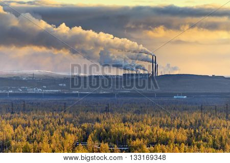 Smokestack smokestacks that pollute the atmosphere. Ecological catastrophy. Polar tundra deep autumn. Sunset bad lighting conditions.