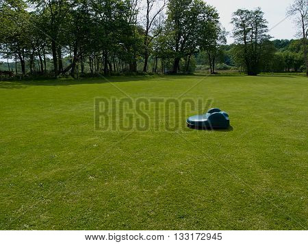 Giant size industrial robotic lawn mower on grass in a city park