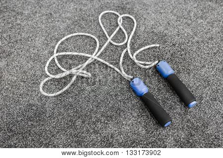 Skipping rope on grey background top view. Skipping rope on grey carpet after training close-up. White jumping-rope with black and blue grips lays on grey carpet