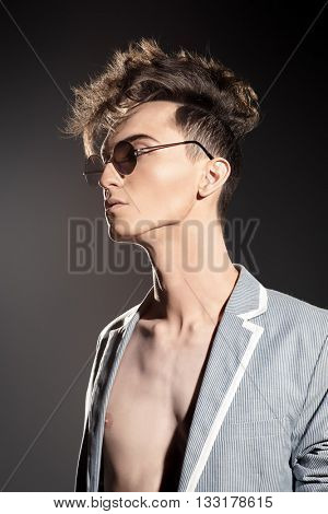 Fashion male model with stylish upright hair and round sunglasses. Beauty, fashion.