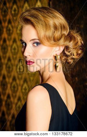 Close-up portrait of a charming young woman with evening make-up and hairstyle over vintage background. Beauty, fashion. Make-up.
