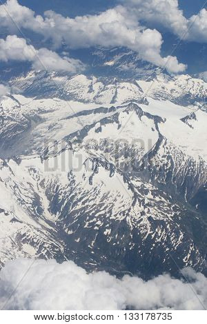 A view from an airplane window on beautiful snowy mountains