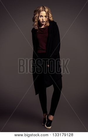 Attractive fashion girl with dark make-up posing in black clothes. Beauty, fashion. Cosmetics.