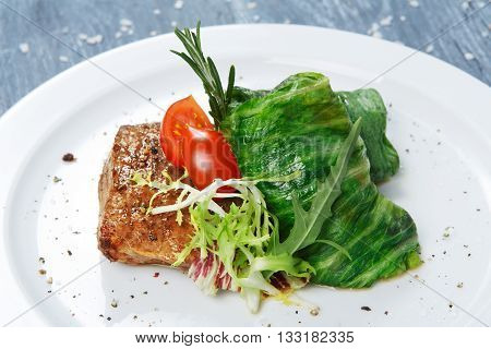 Healthy restaurant food. Creative cuisine. Green stewed Cabbage roll with veal steak. Beef and vegetable. Meat and cabbage with cherry tomato. Restaurant dish served at white plate, closeup.