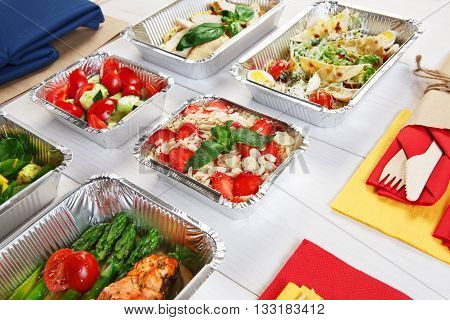 Healthy food delivery. Take away of natural organic low carb diet. Eat right concept, healthy food, clean food take away in aluminium boxes and bag, vegetables and salmon closeup