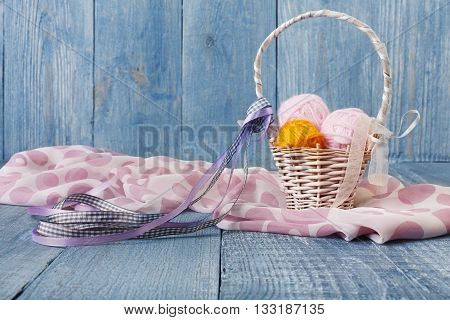 Yarn balls in basket. Knitwork background. Art craft, hand made. Handiwork, knitting, sewing, needlework. Wicker basket with woolen pink and orange balls and silk scarf at blue rustic wood background