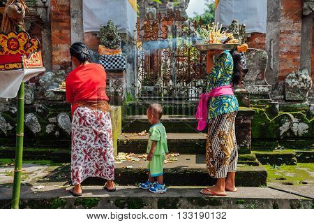 UBUD, INDONESIA - MARCH 01: Balinese women in traditional clothes making offerings in the temple Ubud Bali Indonesia on March 01 2016