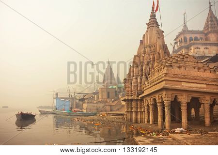 VARANASI, INDIA - JAN 4, 2016: Early morning at Ganges river near the flooded ancient architecture Shiva temple on January 4, 2016. Varanasi urban agglomeration had population of 1435113