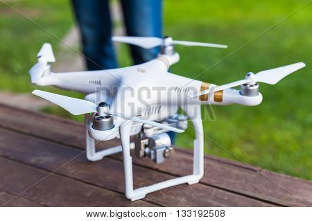 St. Petersburg Russia - May 4 2016: Drone quadrocopter Phantom 3 Professional with high resolution digital camera and remote control designed by the Chinese company DJI stand on a wooden floor