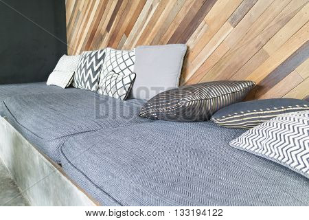 Gray Cushion And Pillow With Slant Wooden Wall