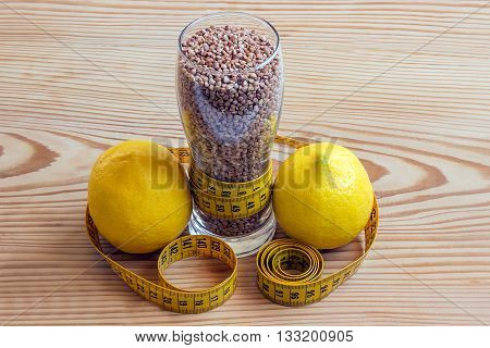 Concept - weight loss. Buckwheat measuring tape and colorful fresh lemons