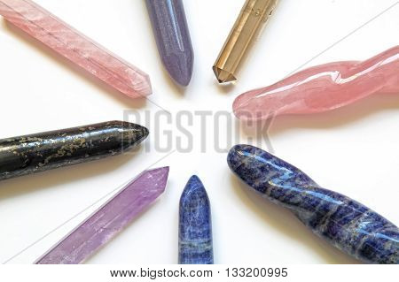8 different healing crystal wands - a wheel spoke arrangement with an empty center displaying eight crystal wands including rose quartz, smokey quartz, amethyst, sodalite, lapis on white background