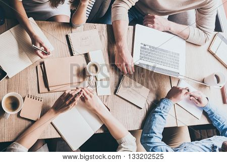 Business meeting concept. Top view close-up image of business people working together while sitting at the desk in office
