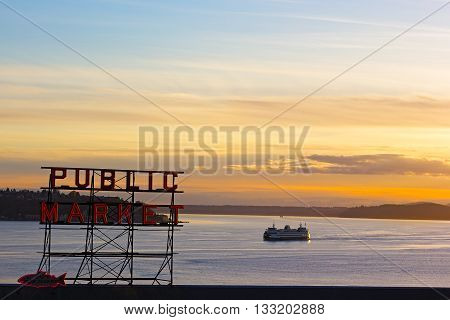 SEATTLE USA - MARCH 25 2016: Sunset over Puget Sound in Seattle on March 25 2016. Pike Public Market neon sign at sunset.