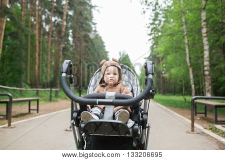 Baby in sitting stroller on nature. Adorable one year-old child with a stroller walk in a green summer forest
