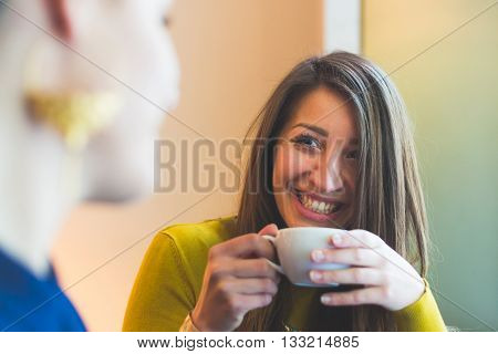 Two women in a cafe smiling and looking each other. One is blurred on the left and the other woman is looking at her smiling and holding a cup of coffee. She looks candid with a beautiful smile.