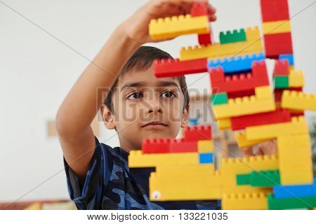 Little Indian boy concentrated on building a tower