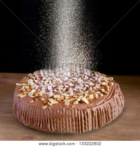 sweet cake with falling sugar on dark wooden background